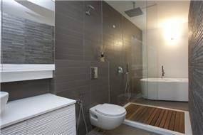 חדר רחצה שכולל אמבטיה ומקלחון צמודים. עיצוב של ענבל ברקוביץ