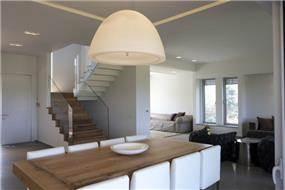 מבט מקיף אל פינת אוכל, סלון ומדרגות בעלי חומרים וצבעוניות משותפת. עיצוב: ענבל ברקוביץ
