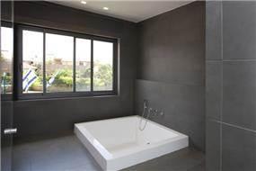 חדר אמבטיה בעיצוב מינימליסטי וריצוף כהה. עיצוב: ענבל ברקוביץ
