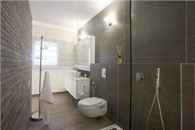 חדר רחצה עם ריצוף וחיפוי קיר חומים. עיצוב של ענבל ברקוביץ
