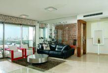 סלון וחדר עבודה עם מחיצת זכוכית בנייהם בדירה בגבעתיים