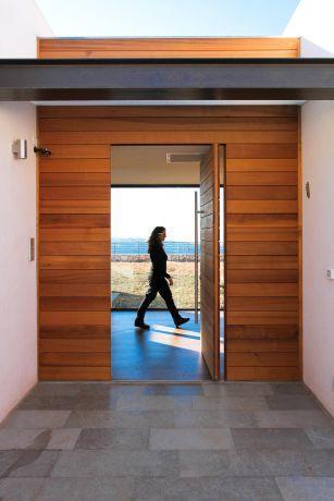 דלת כניסה מעץ ומערכת קיר מחופה עץ סביב. עיצוב saab architecs