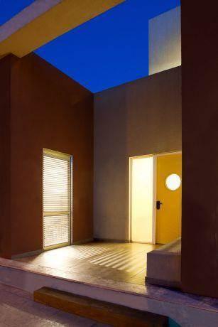 משחק של תאורה במבנה חצי סגור וחצי פתוח של כניסה לבית. עיצוב של saab architects