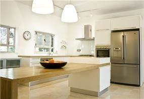 מטבח מודרני בקווים נקיים עם משטח גדול לעבודה ואכילה. עיצוב: saab-architects