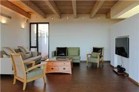 קורות עץ חשופים בתקרה, פרטי ריהוט מעניינים ועיצוב מינימלי בסלון. saab architects