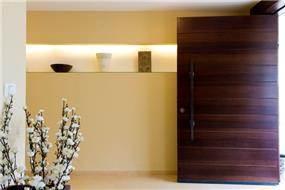 """דלת כניסה מעץ """"פיווט"""" ונישת גבס עם תאורה. עיצוב של SaaB architects"""