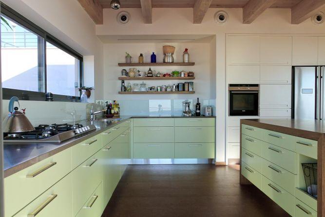 מטבח הכולל אי עבודה גדול עם בוצ'ר. עיצוב של saab architects