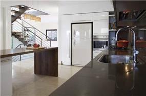מבט מהמטבח לעבר החלל הציבורי בבית והמדרגות. עיצוב של saab architects