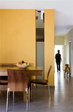 פינת אוכל בצבעים חמים ומבט אל המסדרון. עיצוב של saab architects