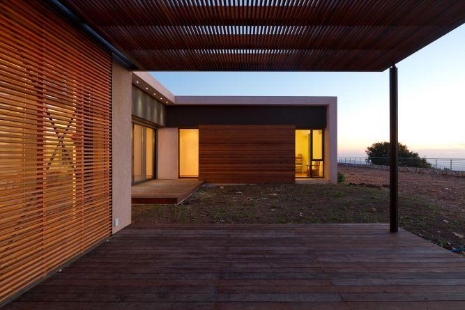 חצר בית מעוצבת, הכוללת דק, פרגולה ורפפות עץ. עיצוב של saab architects