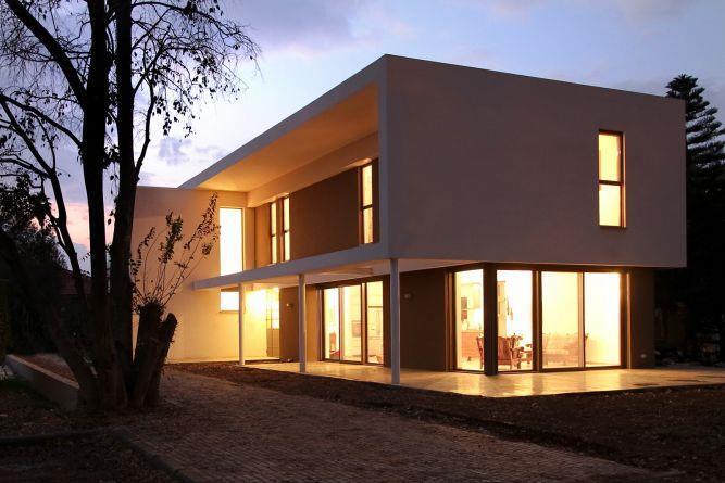 האור מעבר לחלונות הגדולים מעצים את תחושת ה''ריחוף'' של התיבה הלבנה בחשכה. בית פרטי בעיצוב saab architects