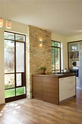 אי במטבח הכולל שילוב חומרים:עץ, בריקס מפרוק וריצפת פרקט. עיצוב של saab architects