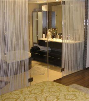 סווי טת הורים בדירה ברמת אביב.קיר זכוכית מפריד בין האמבטיה לחדר השינה