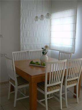 שילוב של שולחן אוכל מעץ אלון עם כסאות לבנים ווילון.עיצוב של רויטל רודצקי
