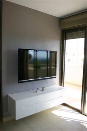 קיר טלויזיה מודרני המשלב נגיעה של צבע, בעיצוב איילת רפאלי