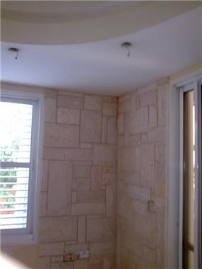 קיר מחופה עם ספוטים בנישת גבס מעל עבודת אומנות הצבע והגבס