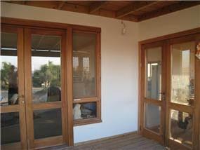 דלתות כניסה מעץ עם חלונות לכניסת אור טבעית מבית נגריית אילן