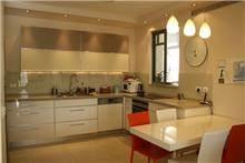 עיצוב מטבח בדירת מגורים, בגווני שמנת עם נגיעות קלות של אדום. אילנה וייס [רבינא וייס הלוי אדריכלים]