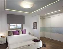 חדר שינה הצמוד לחדר ארונות, המשלב תאורת תקרה, נגרות ופרטי סטיילינג. עיצוב: יוסי שאול YS-DESIGN